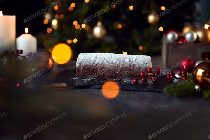 Traditional Yule Log On Table Set For Festive Christmas Meal With Tree Lights In Background
