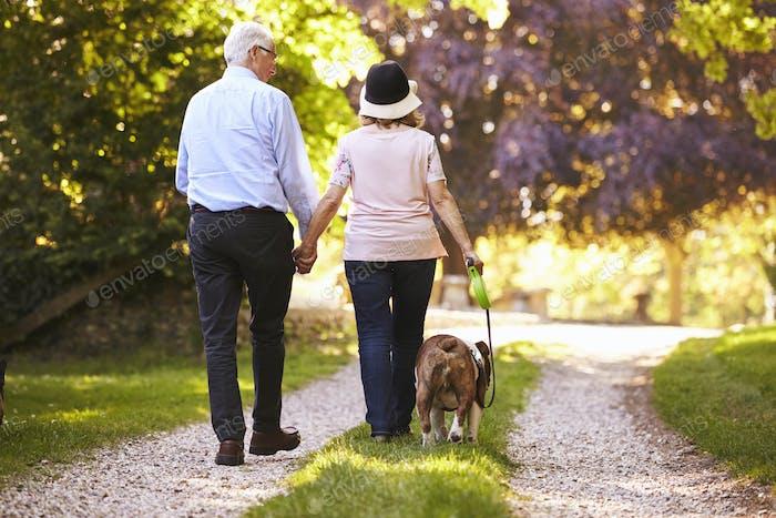 Rear View Of Senior Couple Walking Pet Bulldog In Countryside