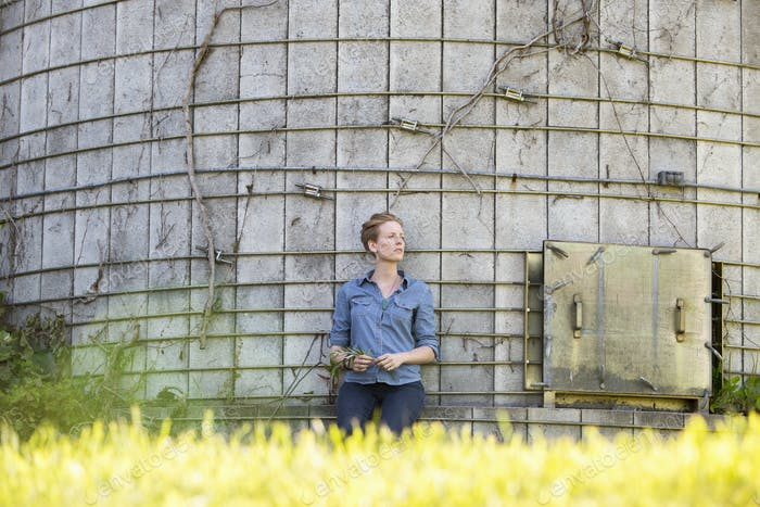 Young woman on a working farm, taking a break in the shade of a silo.