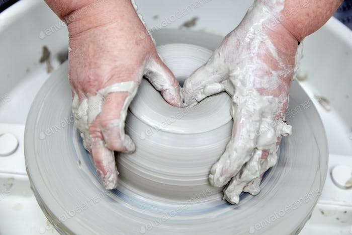 A person using a potter's wheel, throwing a clay pot and using thumbs to shape the wet clay. Seen