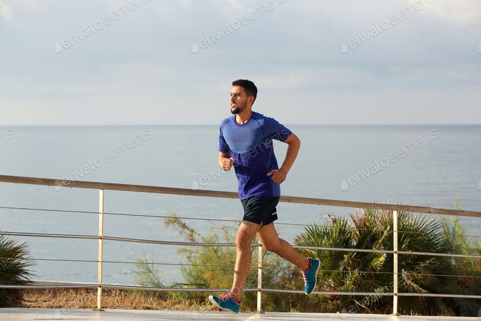 Full length healthy young man running by the sea