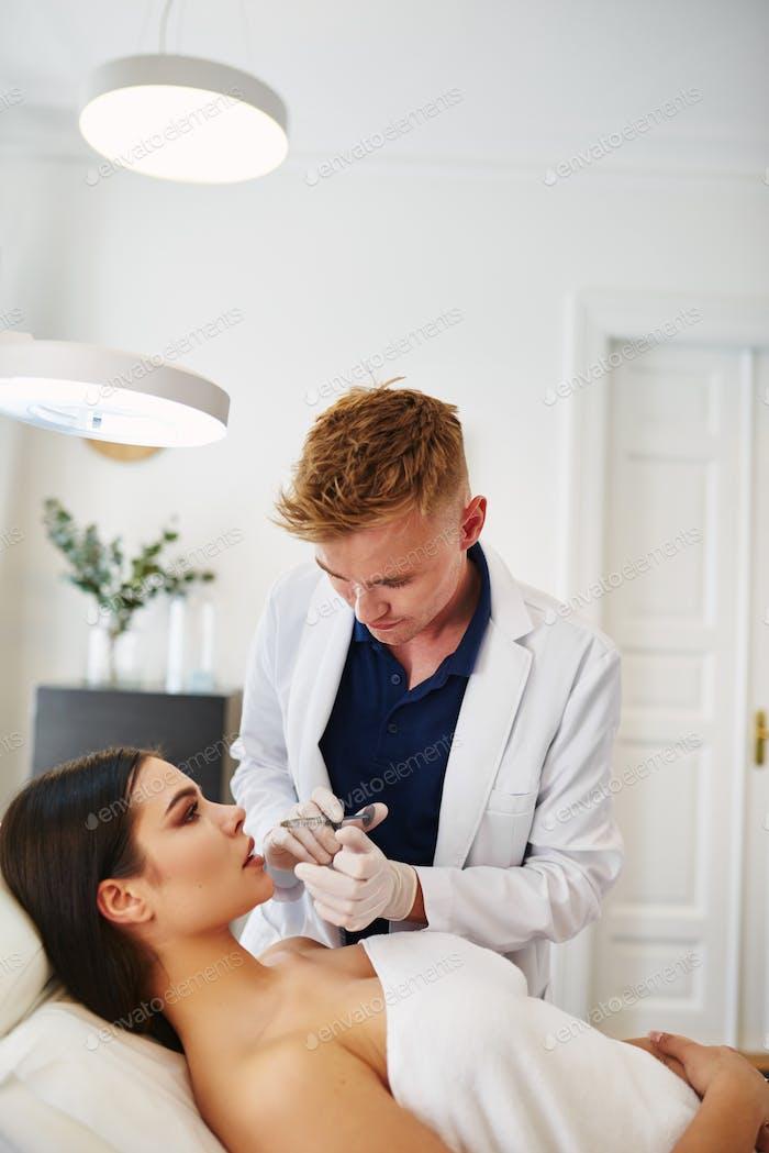 Arzt injiziert Botox in die Lippen eines weiblichen Klienten