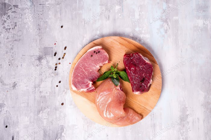 Fresh raw meat - beef, pork and chicken on a wooden background. Lean proteins.