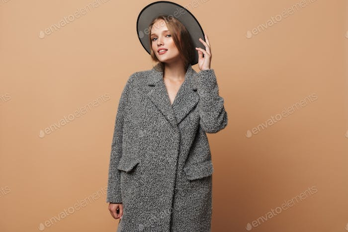 Young beautiful attractive woman with wavy hair in gray hat and coat dreamily looking in camera