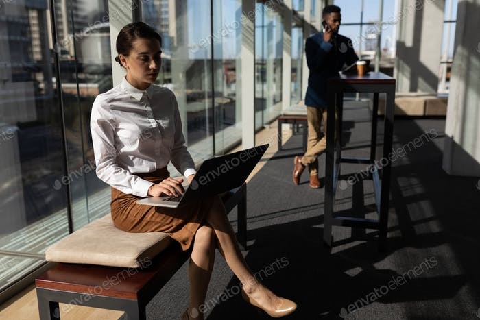Businesswoman using laptop while sitting on bench in modern  office