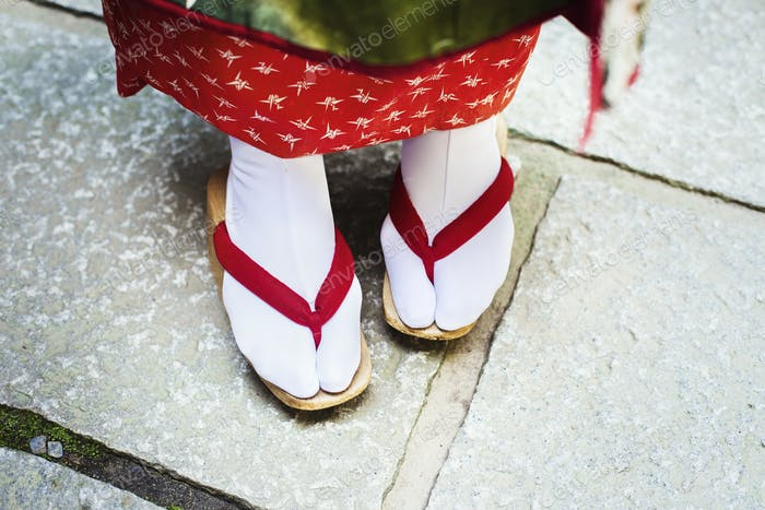 A traditional geisha woman's feet, in wooden soled sandals