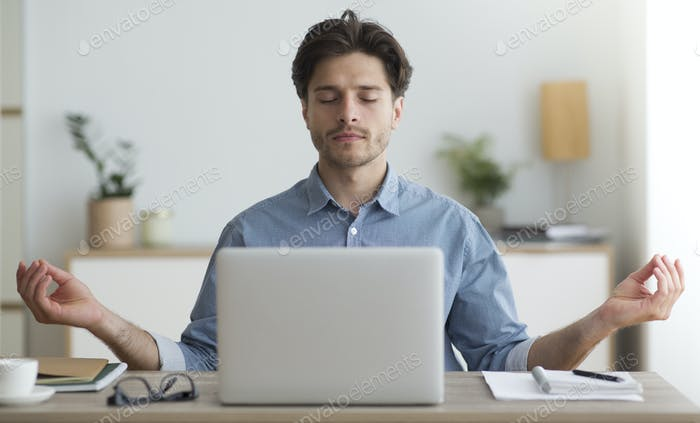Relaxed Man Meditating Sitting At Laptop In Office