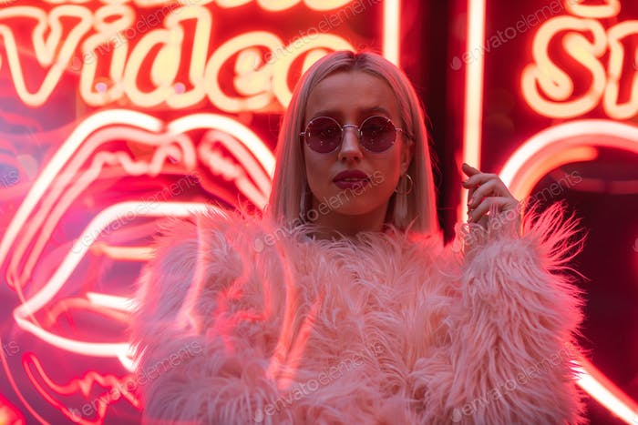 Thumbnail for Cinematic portrait of blond girl with furry pink coat on neon si