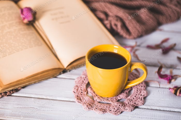 Coffee cup and open book close up. Winter and Christmas time concept.