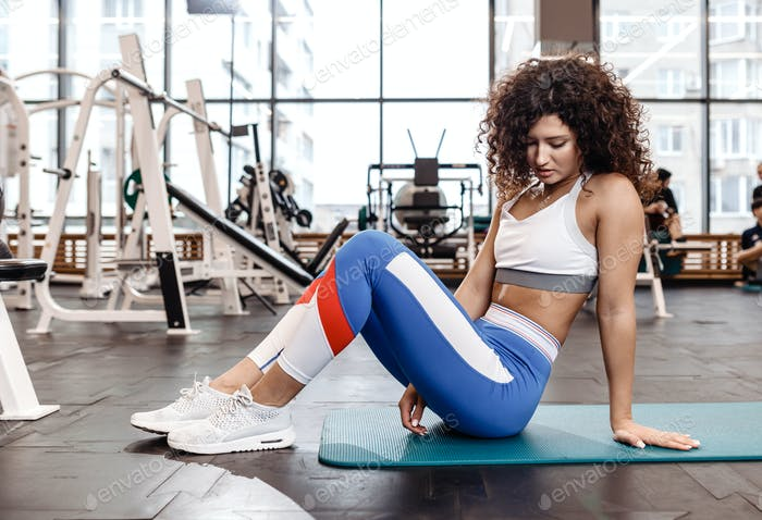 Nice slim curly dark-haired girl dressed in sports clothes is sitting on the mat for fitness in the