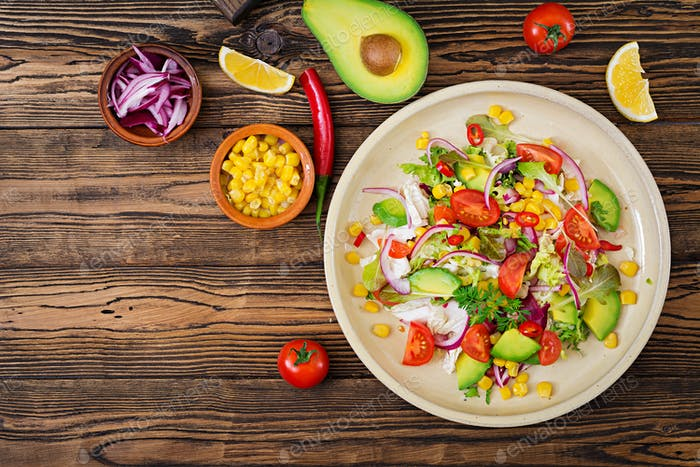 Appetizing vegan salad from tomatoes, avocado, corn, red onion and lettuce leaves