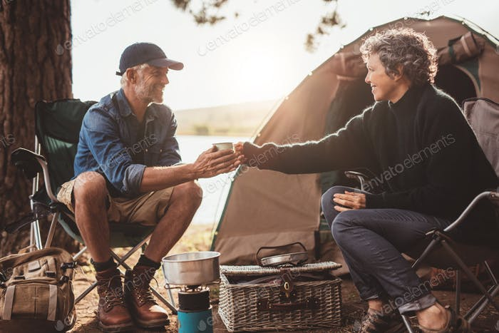Mature couple with coffee camping by a lake