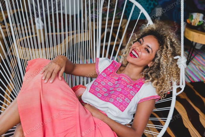 Attractive elegant smiling African American lady on chair