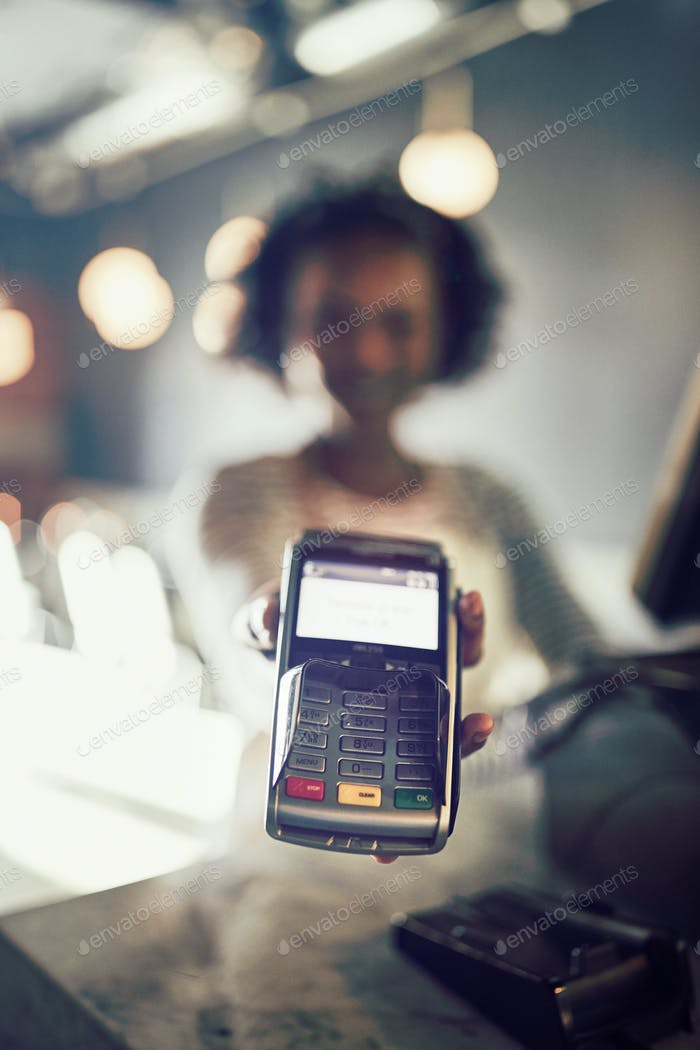 African waitress holding an electronic card machine in a restaurant