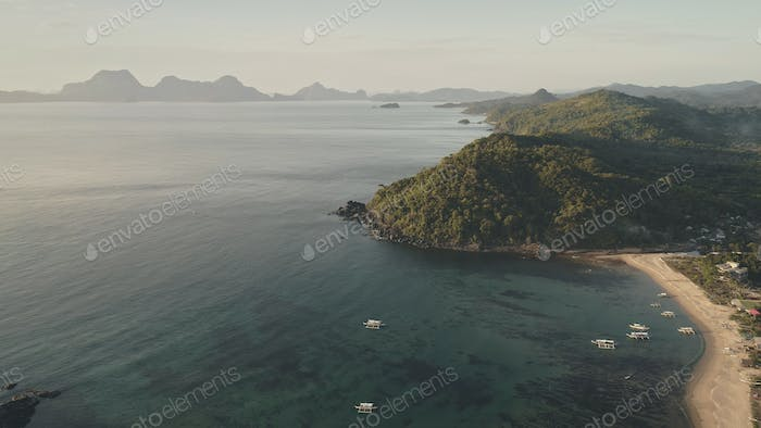 Sun seascape at mist fog aerial. Tropical nobody nature landcape at green forested village buildings