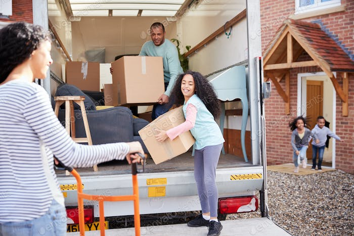 Family Unloading Furniture From Removal Truck Into New Home