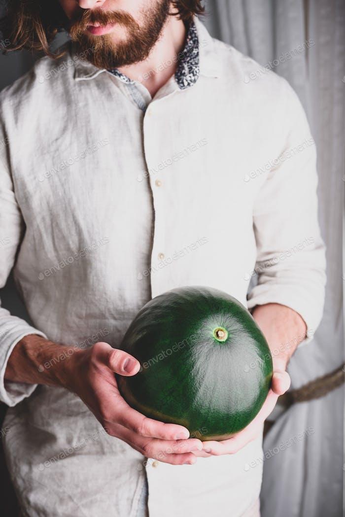 Bärtiger Mann hält ganze Wassermelone