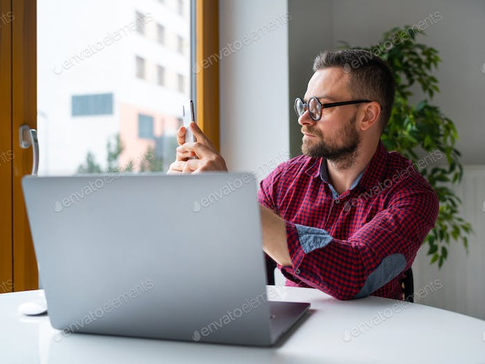 Man in glasses sitting at home office and working on a laptop an