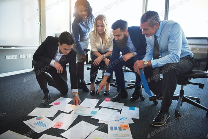 Corporate executives brainstorming with paperwork on an office floor
