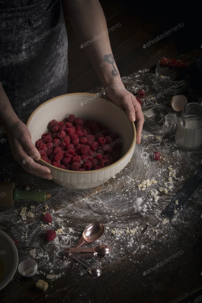 Valentine's Day baking, woman preparing fresh raspberries in a bowl.