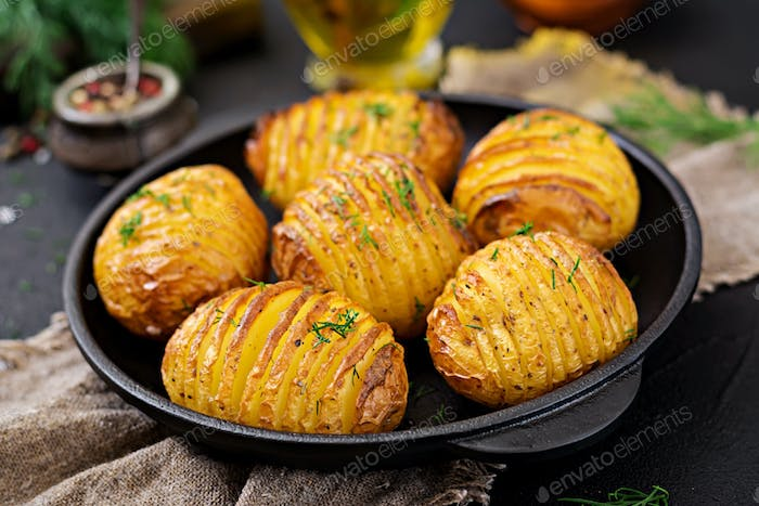 Baked potato with herbs on black background. Vegan food. Healthy meal.