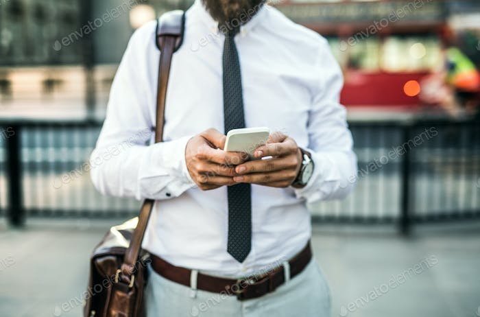 Unrecognizable businessman with smartphone standing on the street in city.