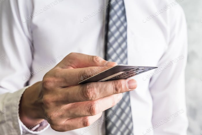 Close up of businessman holding credit card.