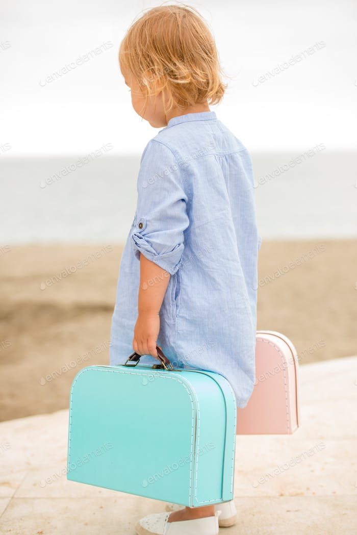 Little girl carrying her suitcases at the seaside