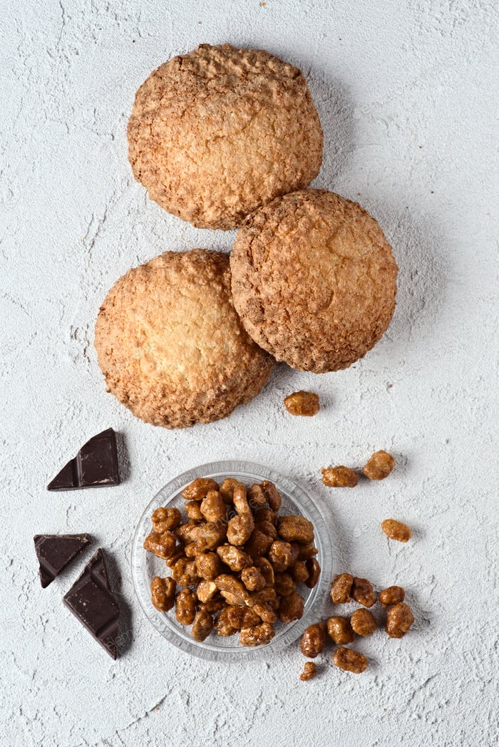caramelized chocolate peanuts and pastries on white rustic background