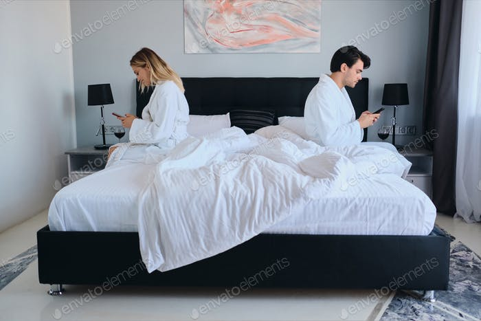 Thoughtful man and attractive woman in bathrobes using cellphones sitting on different sides of bed