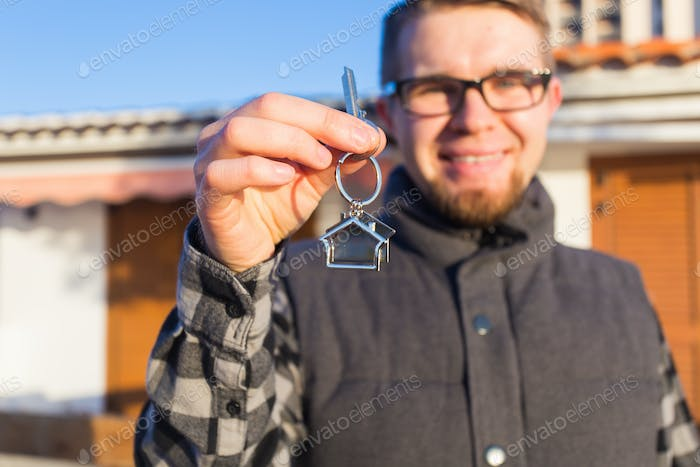 Dwelling, buying home, real estate and ownership concept - handsome man showing his key to new home