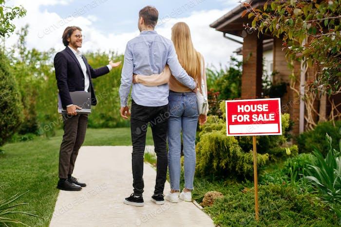 Immobilienmakler zeigt Haus zu verkaufen an junges Paar, außerhalb