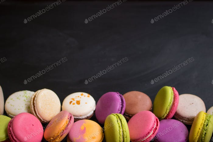 Assorted colorful macaroons on a dark background