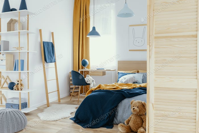 Messy kid's bedroom with toys and wooden furniture real photo