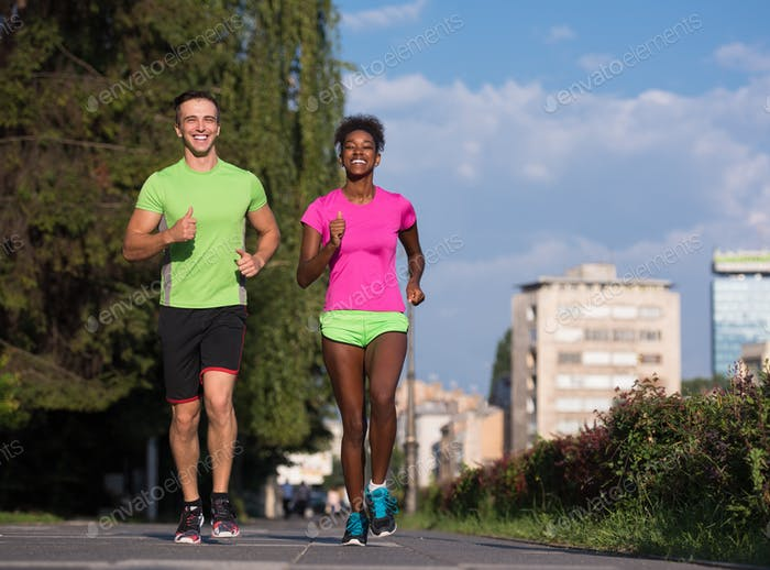 young smiling multiethnic couple jogging in the city
