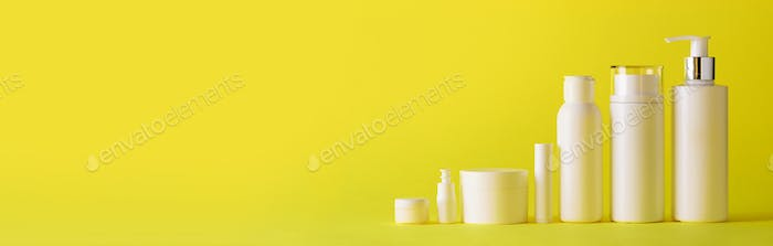 White cosmetic tubes on yellow background with copy space. Skin care, body treatment, beauty concept