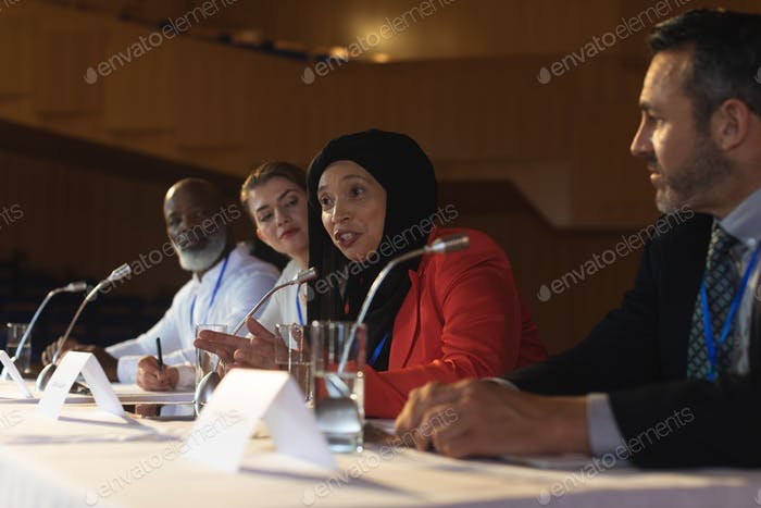 Mixed race businesswoman with executive speaking in speaker while sitting in the auditorium