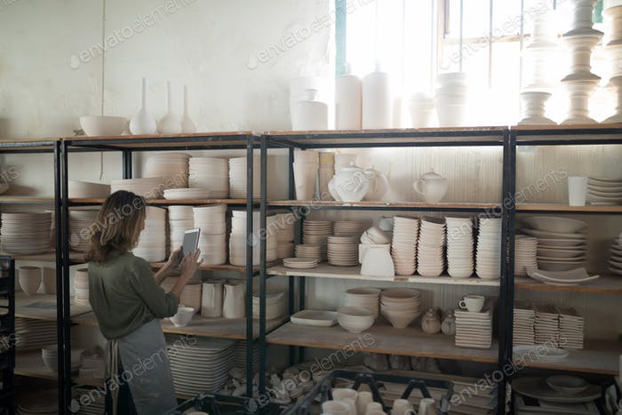 Female potter using digital tablet near shelf