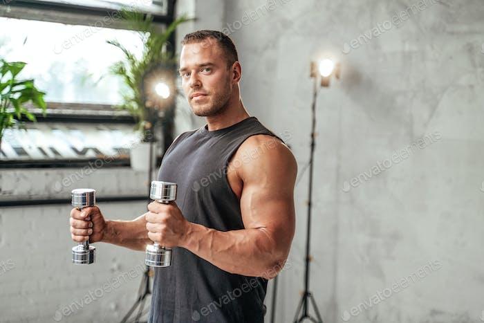 Attractive bodybuilder training with dumbells in studio room