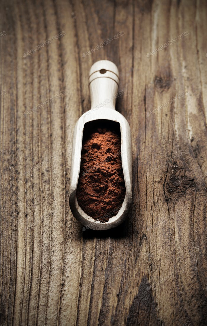 Wooden spoon full of cocoa powder