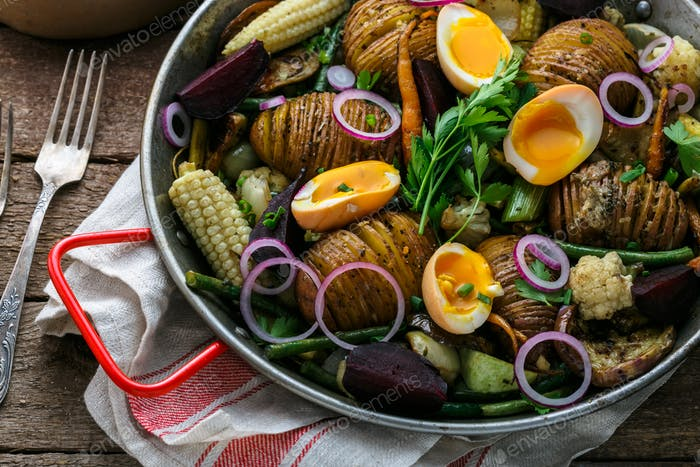 Close view of hasselback potatoes and baked vegetables