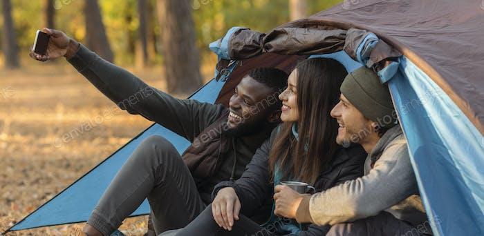 Caminantes alegres tomando selfie en el teléfono inteligente, sentado en la tienda de campaña