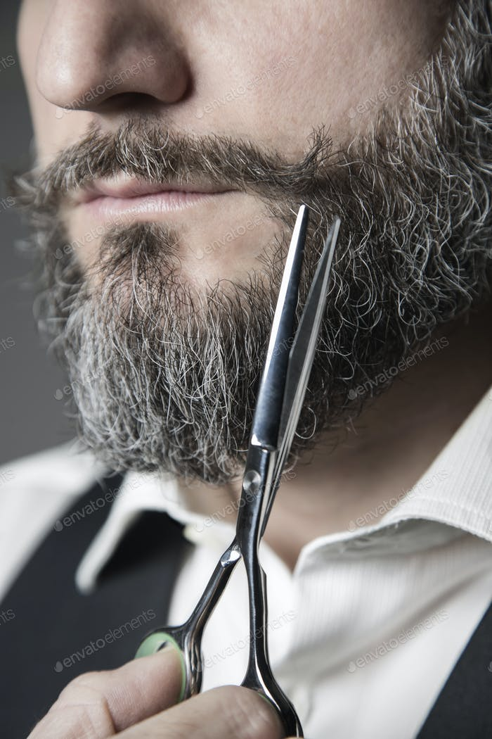 close up of a barber adjusting his mustache with a pair of sciss