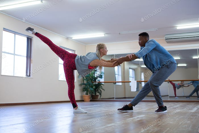 Full length of dancers rehearsing on wooden floor