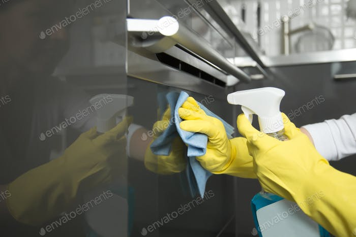 Closeup of female hands in gloves cleaning oven, holding spray