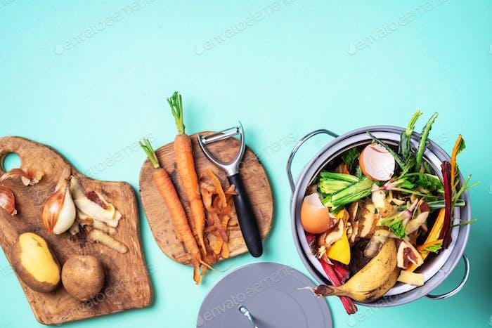 Müllsortierung. Biologische Lebensmittelabfälle aus Gemüse, bereit zum Recycling im Kompostbehälter auf blau