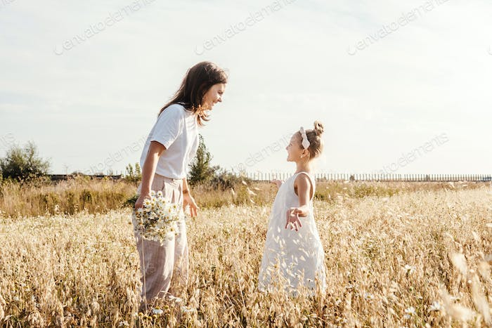 Young mother and daughter having fun outdoor.
