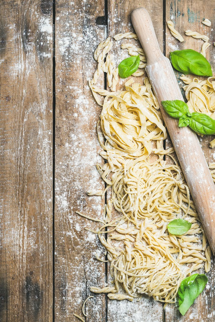 Various homemade fresh uncooked Italian pasta with flour, basil