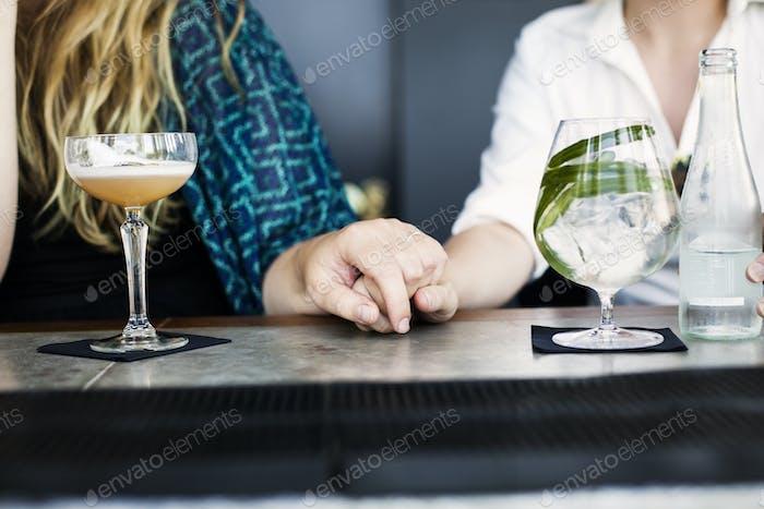 Mittelteil der lesbischen Paar Hand mit Gläsern Cocktail auf der Bar Theke