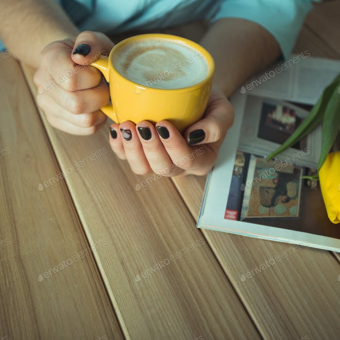Yellow cup in the hands of women. Gel nail manicures. Phone and the magazine on the table
